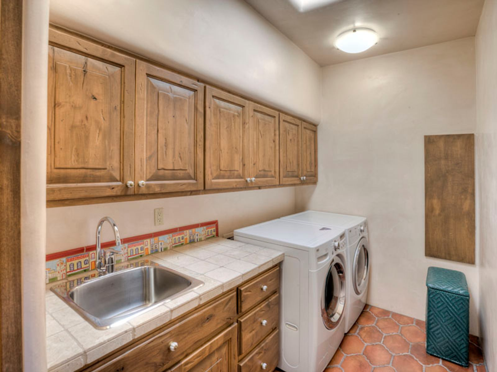 Laundry rm boasts plentiful cabinets, drawers