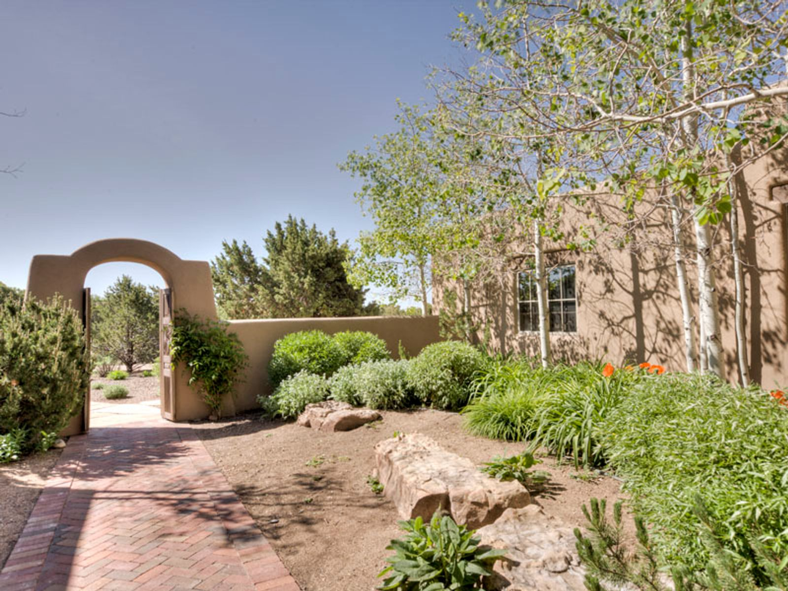 Encircled by a classic adobe wall and wood gate