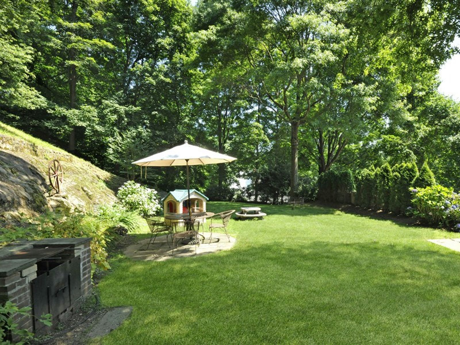 Backyard Features Mature Trees and Buit-in BBQ