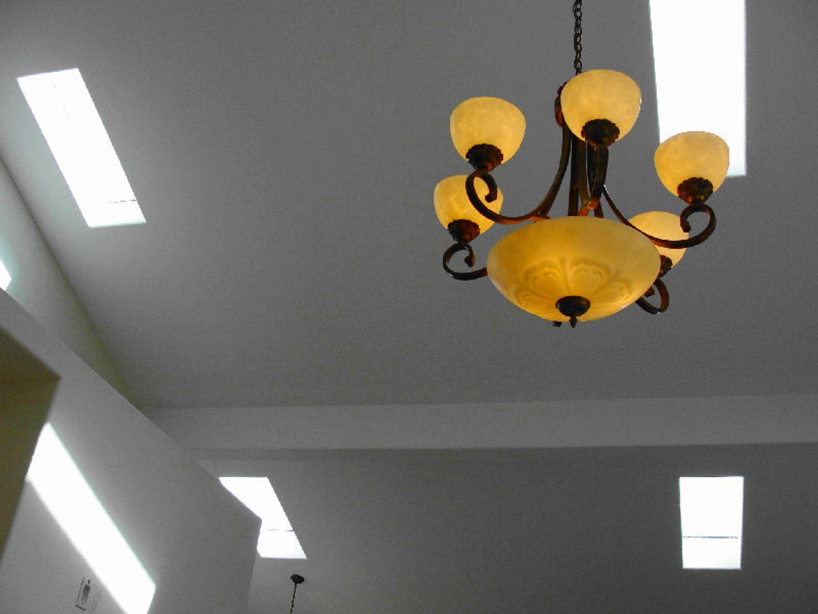 Skylights and chandelier illuminate dining room.